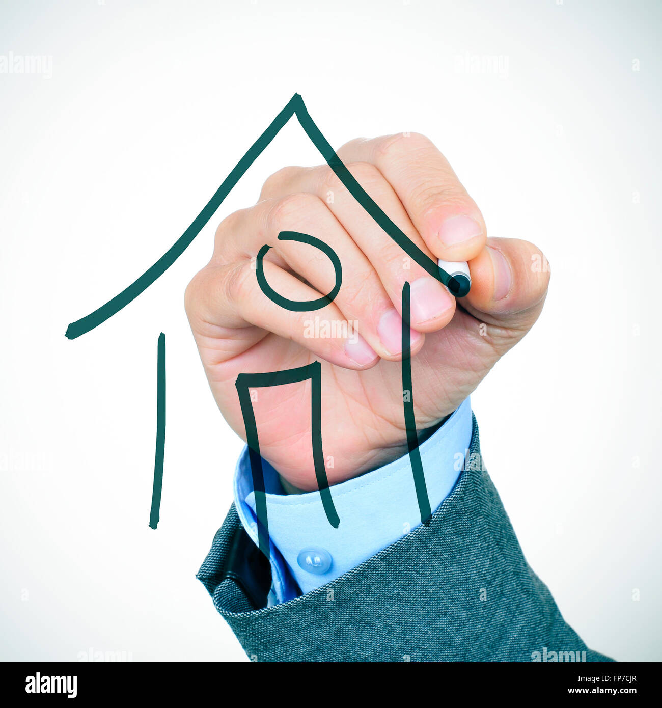 closeup of the hand of a young caucasian businessman in suit drawing a house with a pen in the foreground - Stock Image