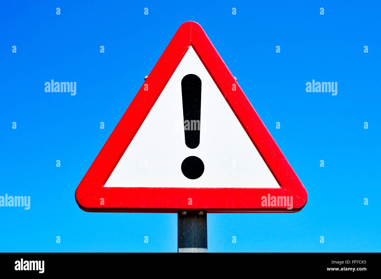 a triangular traffic sign with an exclamation mark against the blue sky - Stock Image