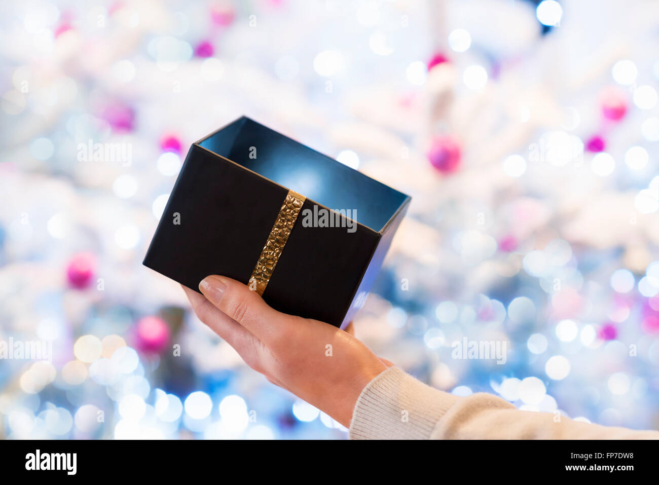 Woman opens a black box gift in front of a Christmas tree - Stock Image