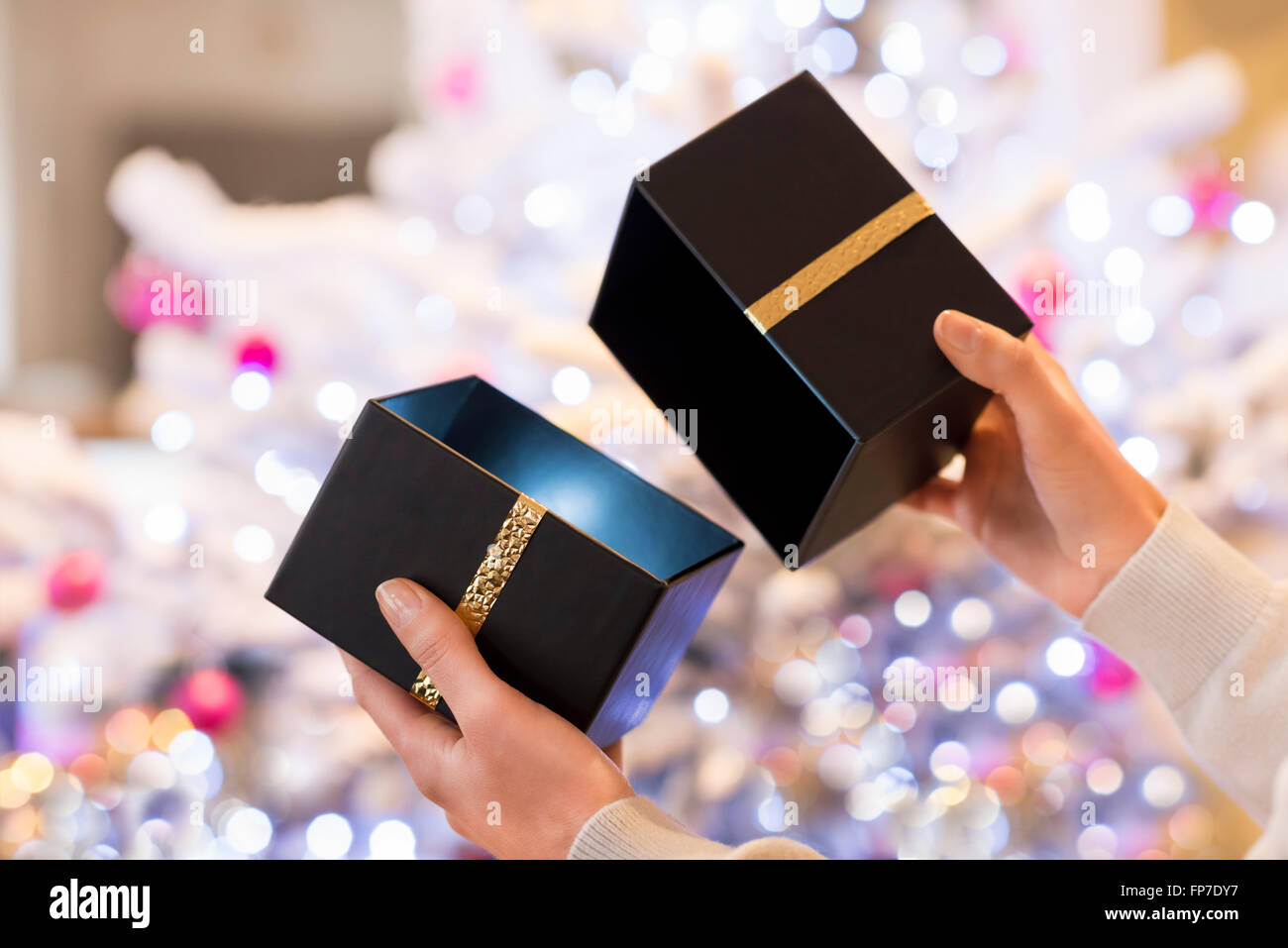 Woman opens a black box present in front of a Christmas tree - Stock Image