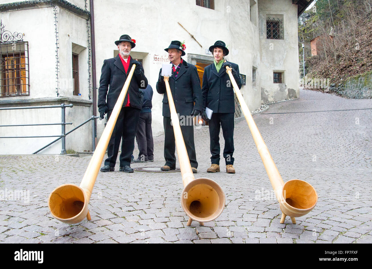 Alphorn players perform in the historic center of Brunico - Stock Image