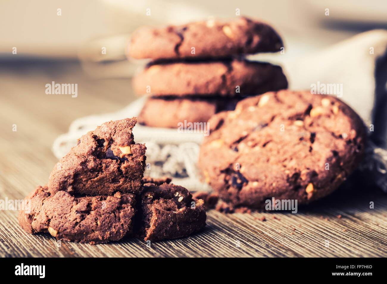 Chocolate biscuit cookies. Chocolate cookies on white linen napkin on wooden table. - Stock Image