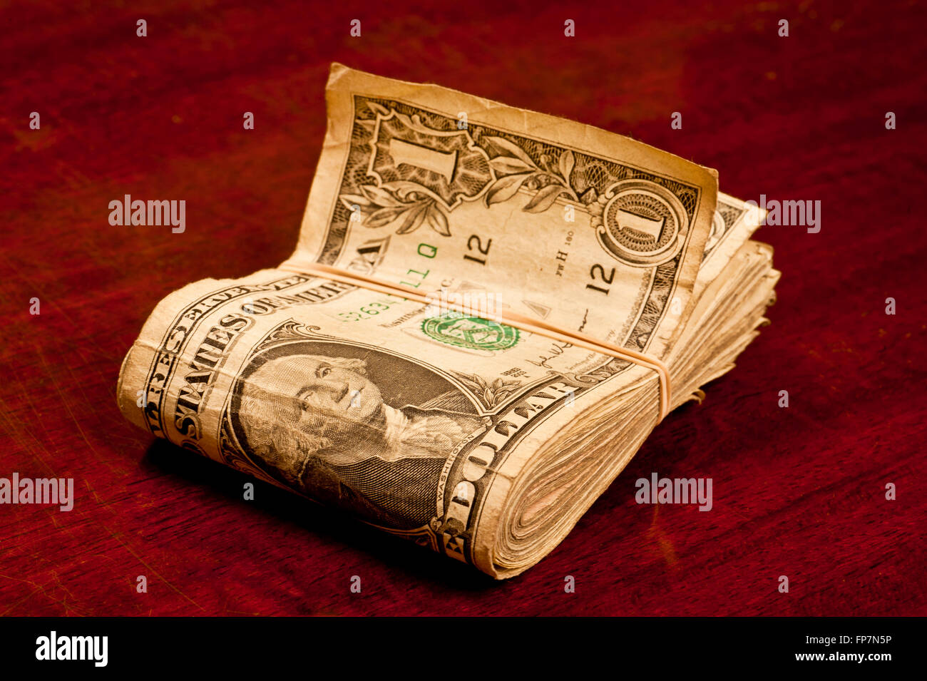 Very Worn Dollar Bills With Rubber Band - Stock Image