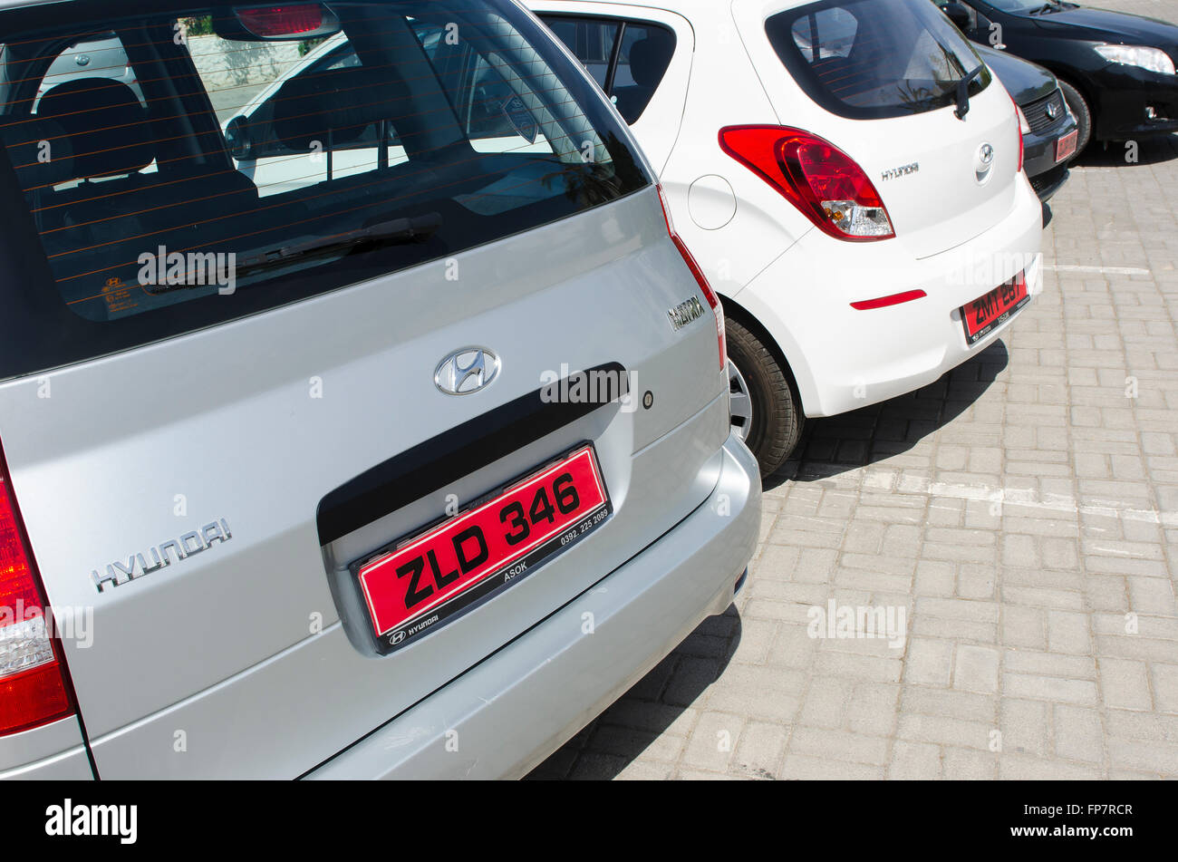 Red number plates on the back of cars parked in a car park in the ...