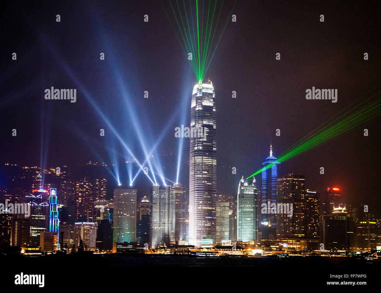 Hong Kong Island skyline seen across Victoria Harbour during the nightly laser show - Stock Image