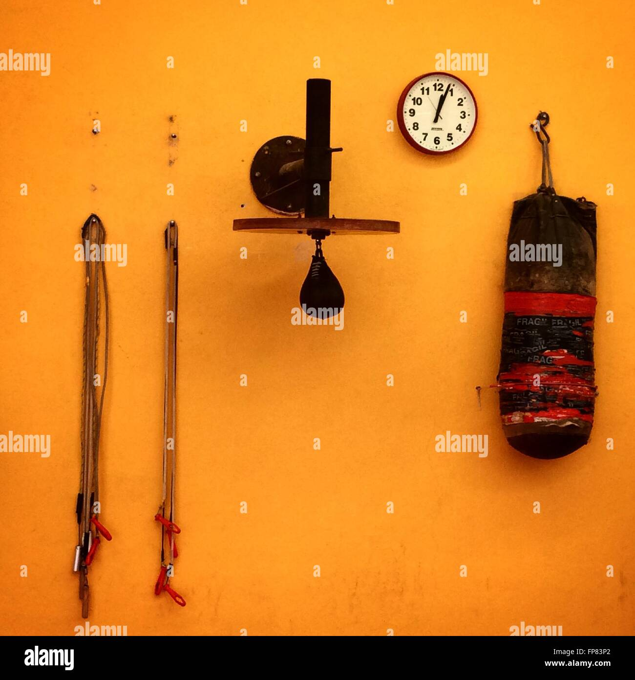 Wall Clock With Boxing Equipment Handing On Orange Wall - Stock Image