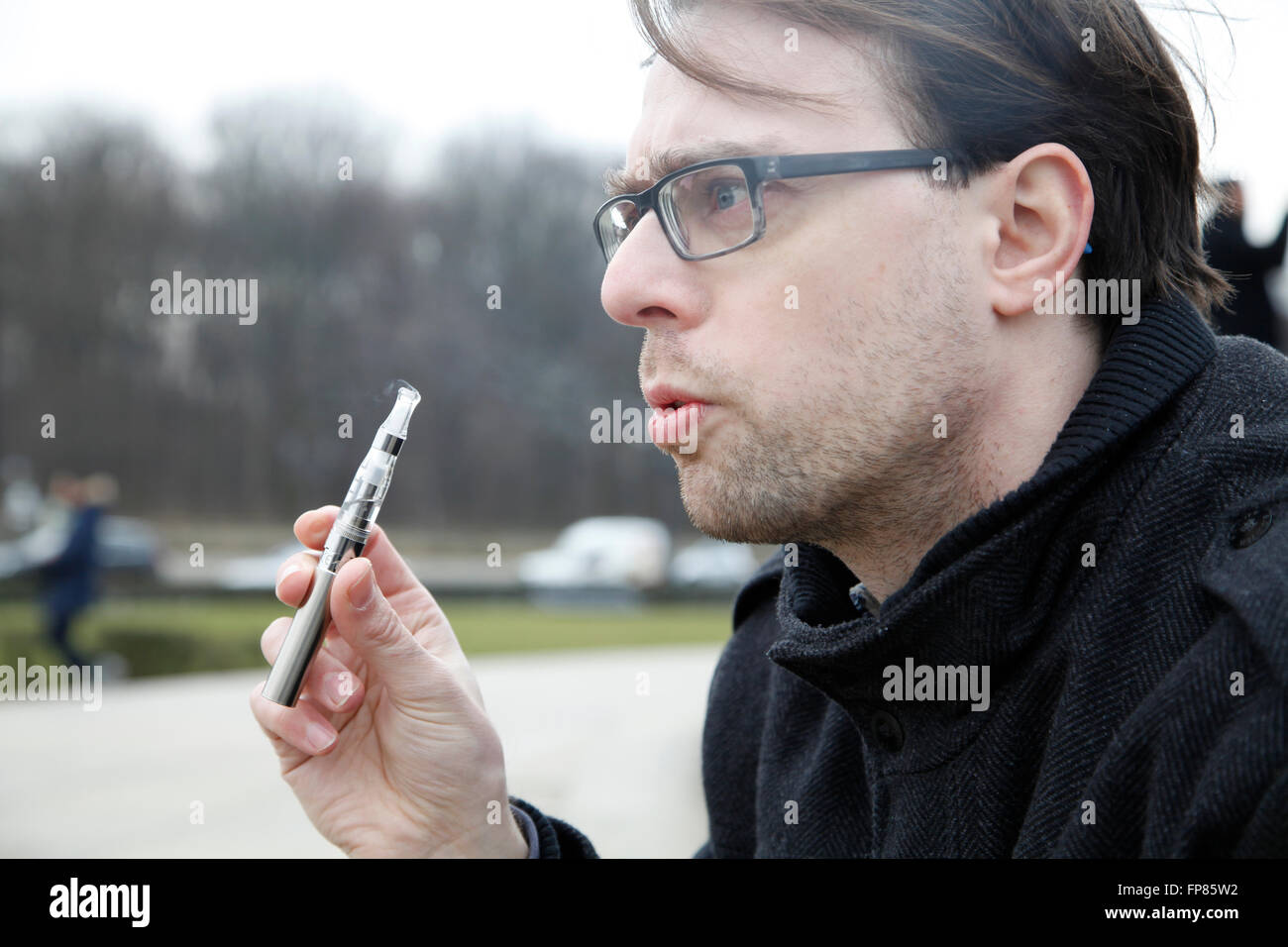 Young man with e-cigarette - Stock Image