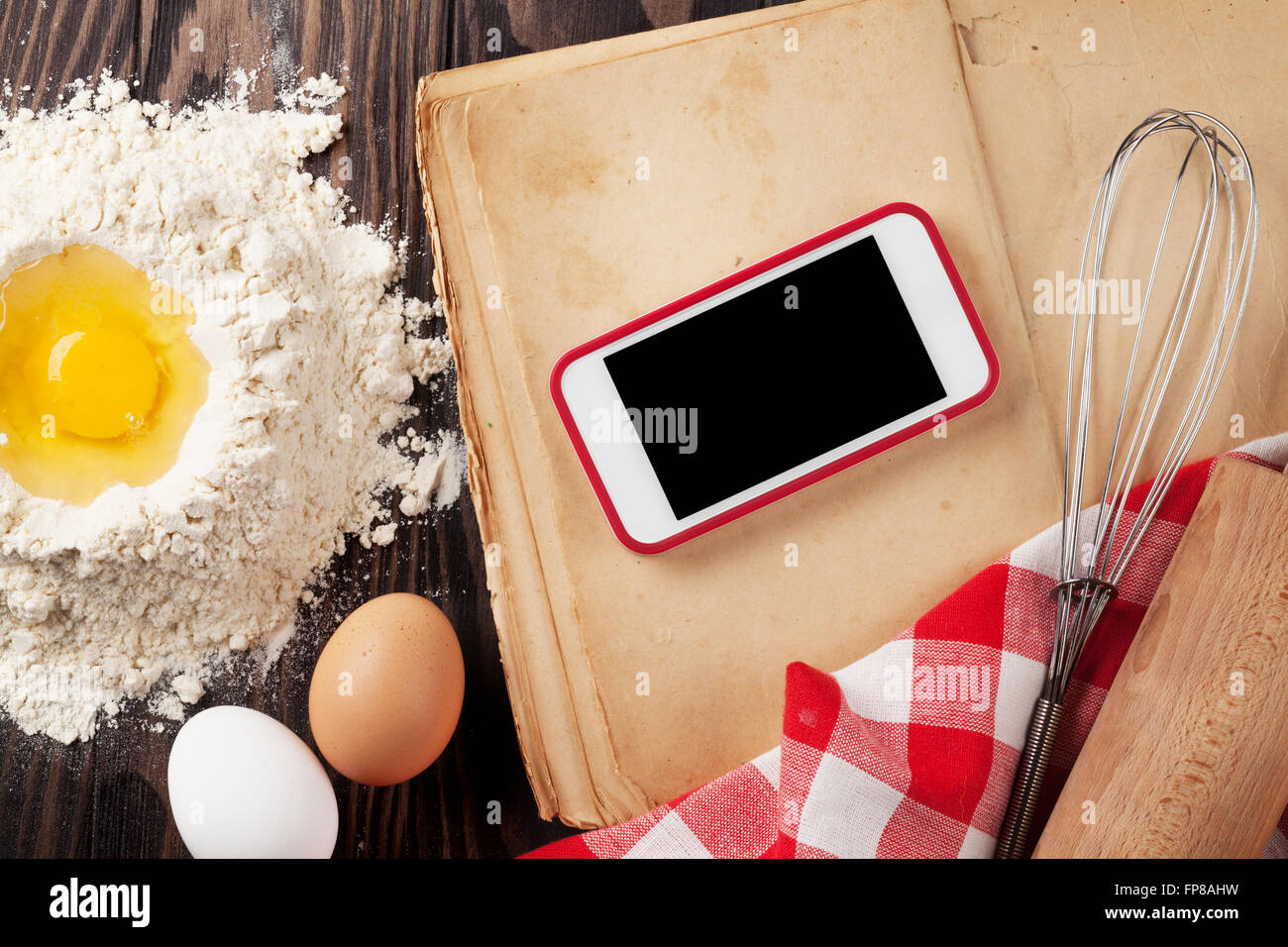 Kitchen table with ingredients utensils and smartphone with blank kitchen table with ingredients utensils and smartphone with blank screen for your app over cooking book on wooden table top vi workwithnaturefo
