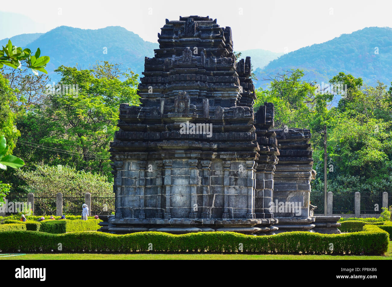 Intricately carved rear of the Mahadev Temple at Tambdi Surla, with beautiful mountains of the Western Ghats in - Stock Image