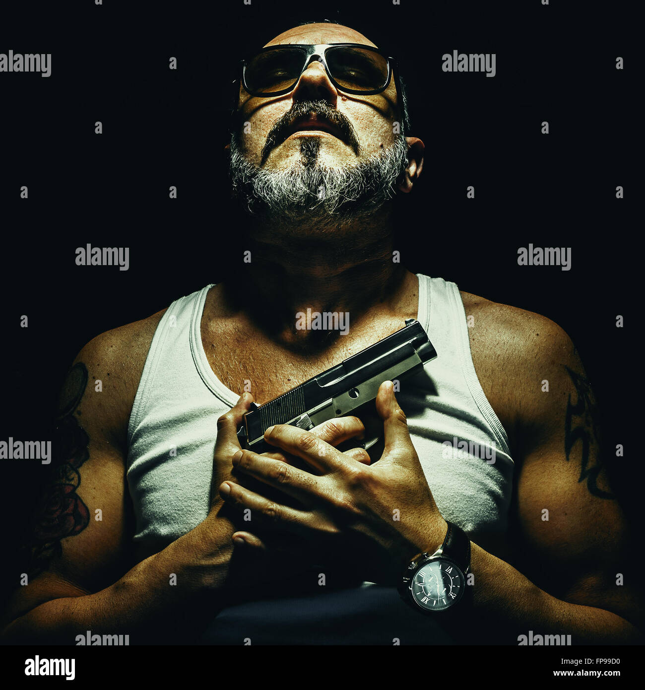 Relaxed and strong man holding a silver pistol on his chests. - Stock Image