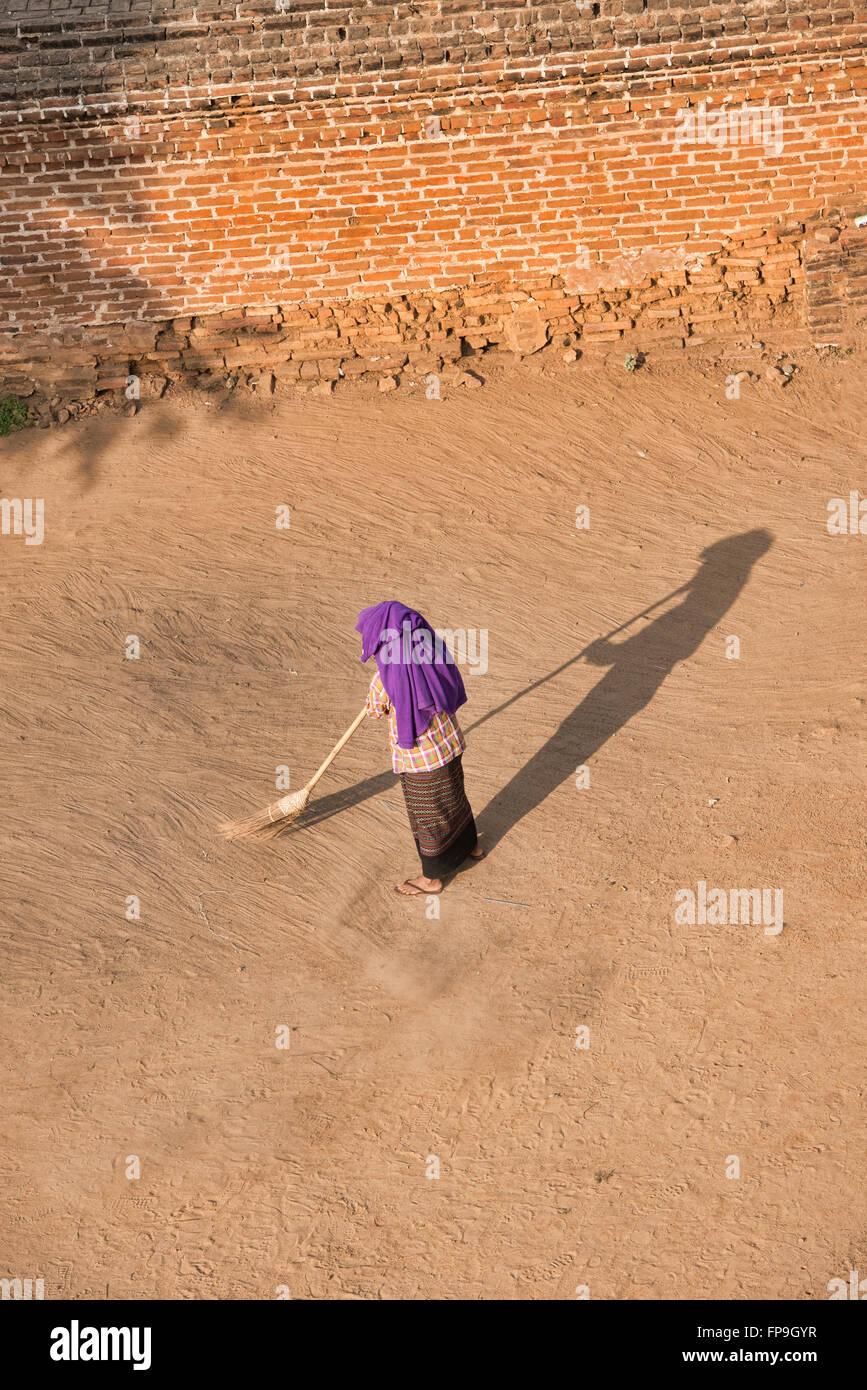 Woman sweeping a temple courtyard, Bagan, Myanmar - Stock Image