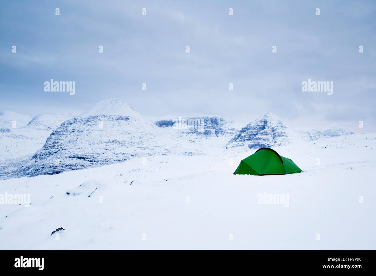 A tent pitched in the snow of the Torridon hills in winter with Beinn Eighe as backdrop, Scotland - Stock Image