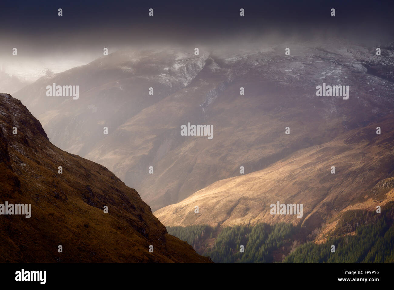 Beinn Bhuide sidelit by dramatic winter light while its summit remains shrouded by snow clouds, Kintail, Scotland - Stock Image