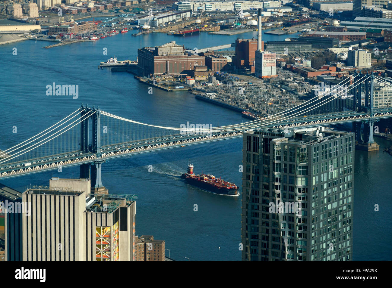 Aerial view of a ship in East River pass under Manhattan Bridge with borough of Brooklyn in background - Stock Image