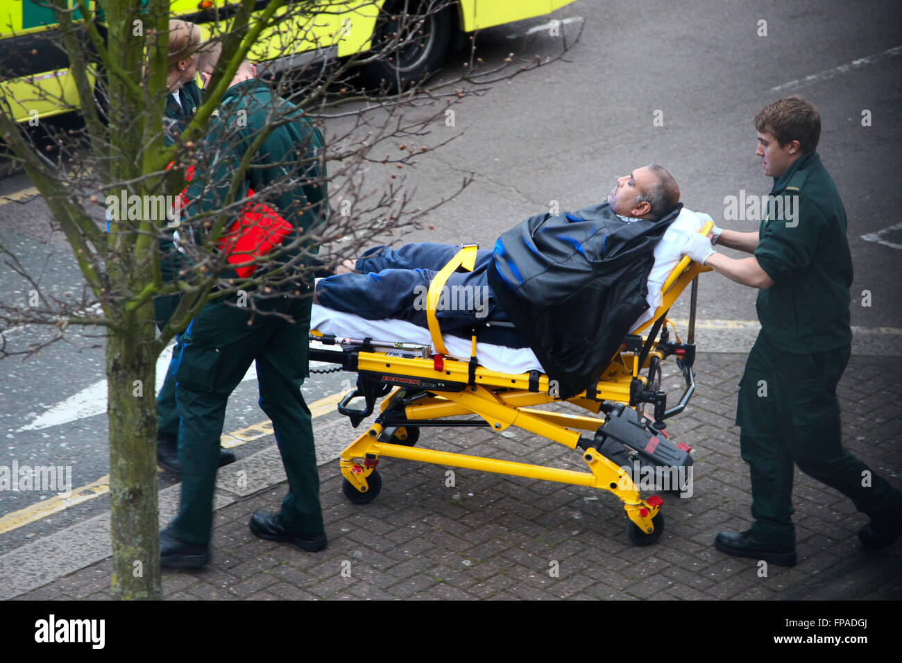 Paramedics wheeling patient on a stretcher into an ambulance in a residential area of North London - Stock Image