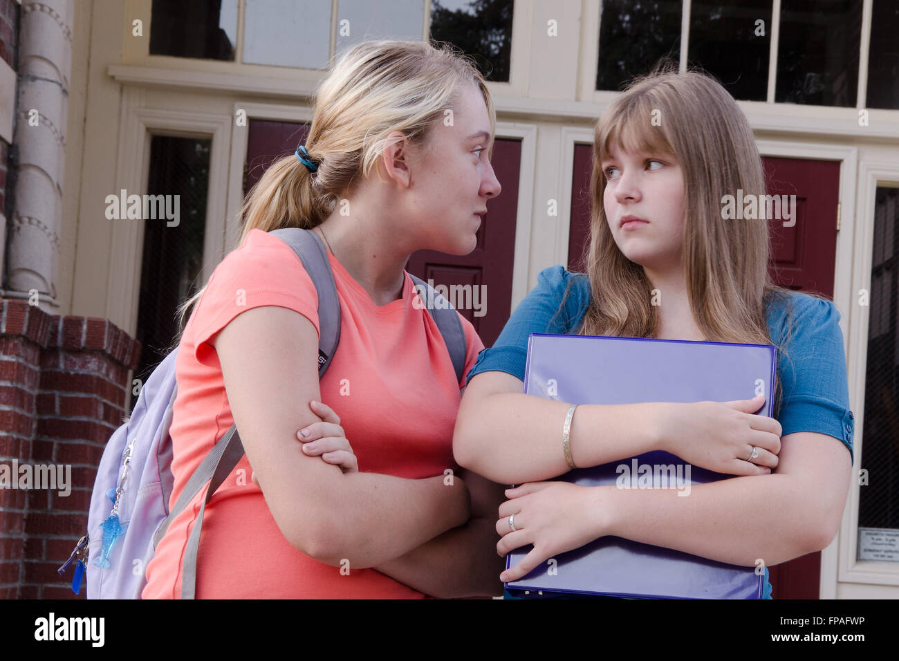 An aggressive teen girl intimidates another girl in front of their school, probably over a boy. - Stock Image