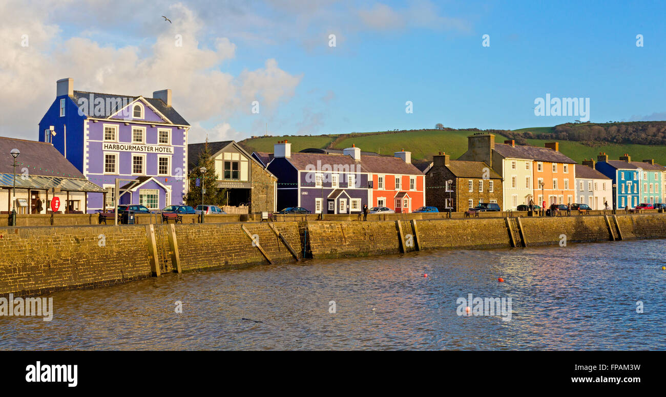 Harbour harbor in Wales UK at sunset showing brightly painted cottages houses and hotel - Stock Image