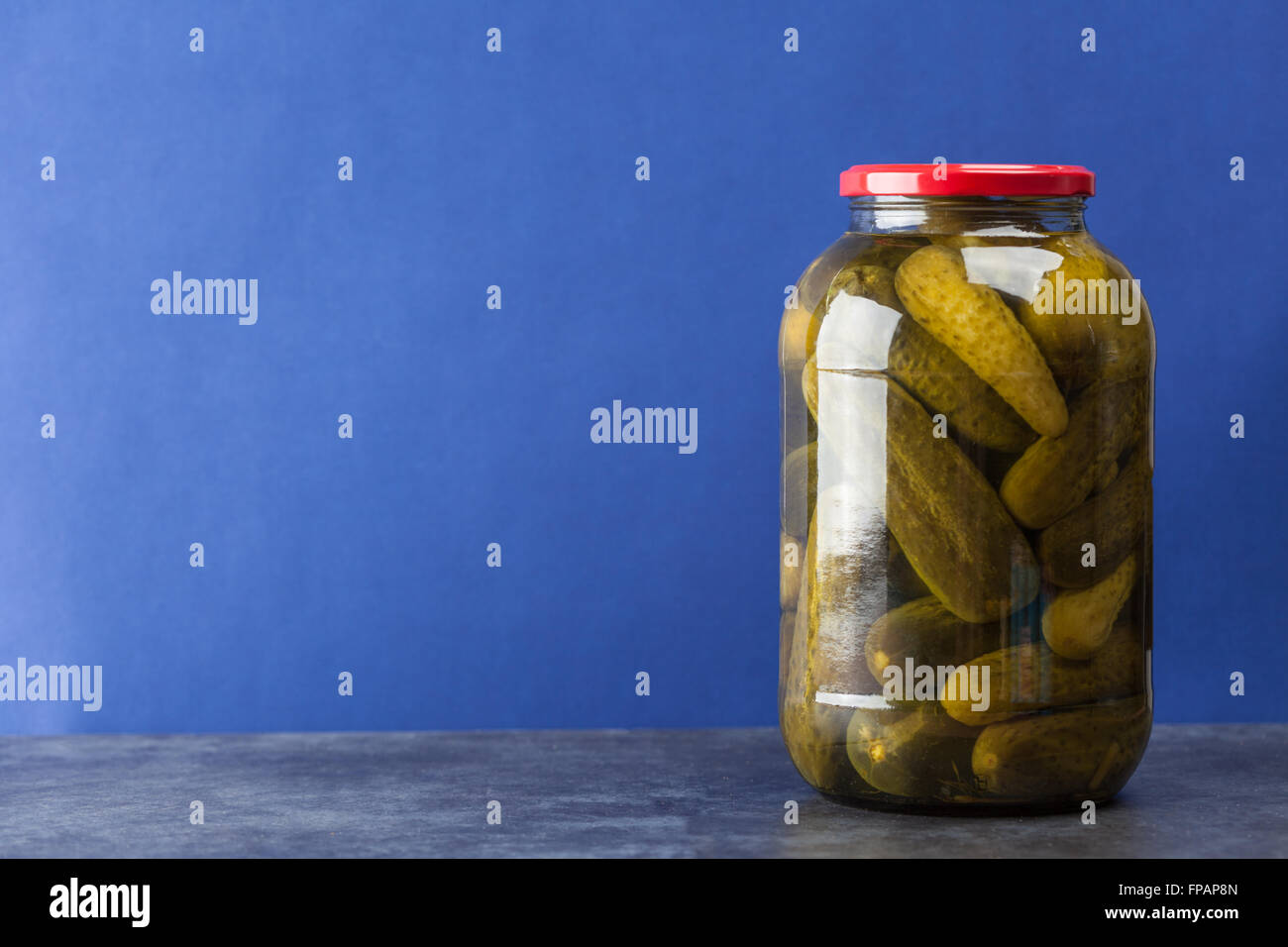 Big jar with pickles on blue background with copy space - Stock Image