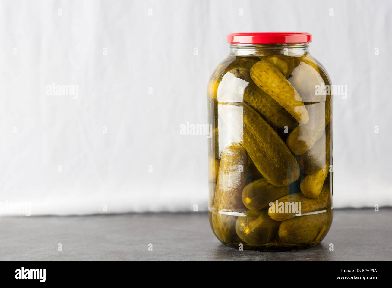 Big jar with dill pickles on white background with copy space - Stock Image