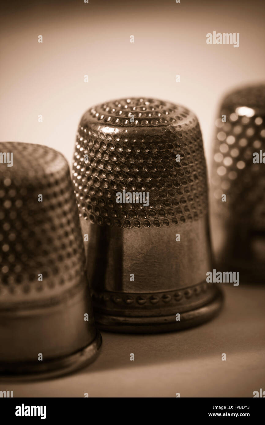 Close-up of three antique thimbles in sepia - Stock Image