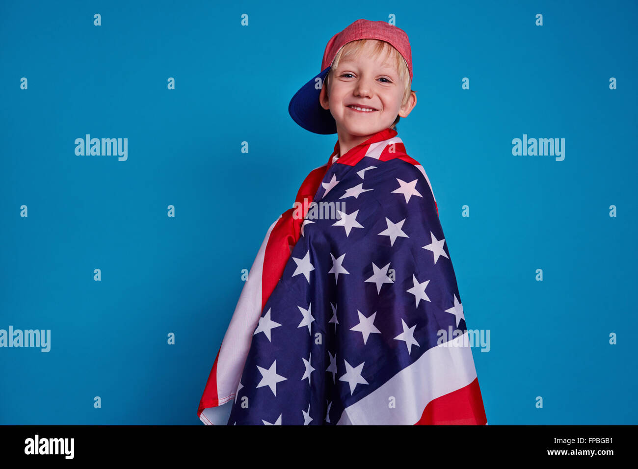 Smiling boy wrapped in American flag isolated on blue background - Stock Image