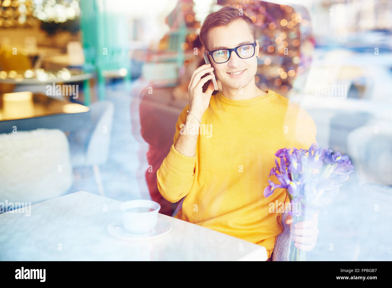 Young man in glasses talking on the mobile phone while sitting in cafe - Stock Image