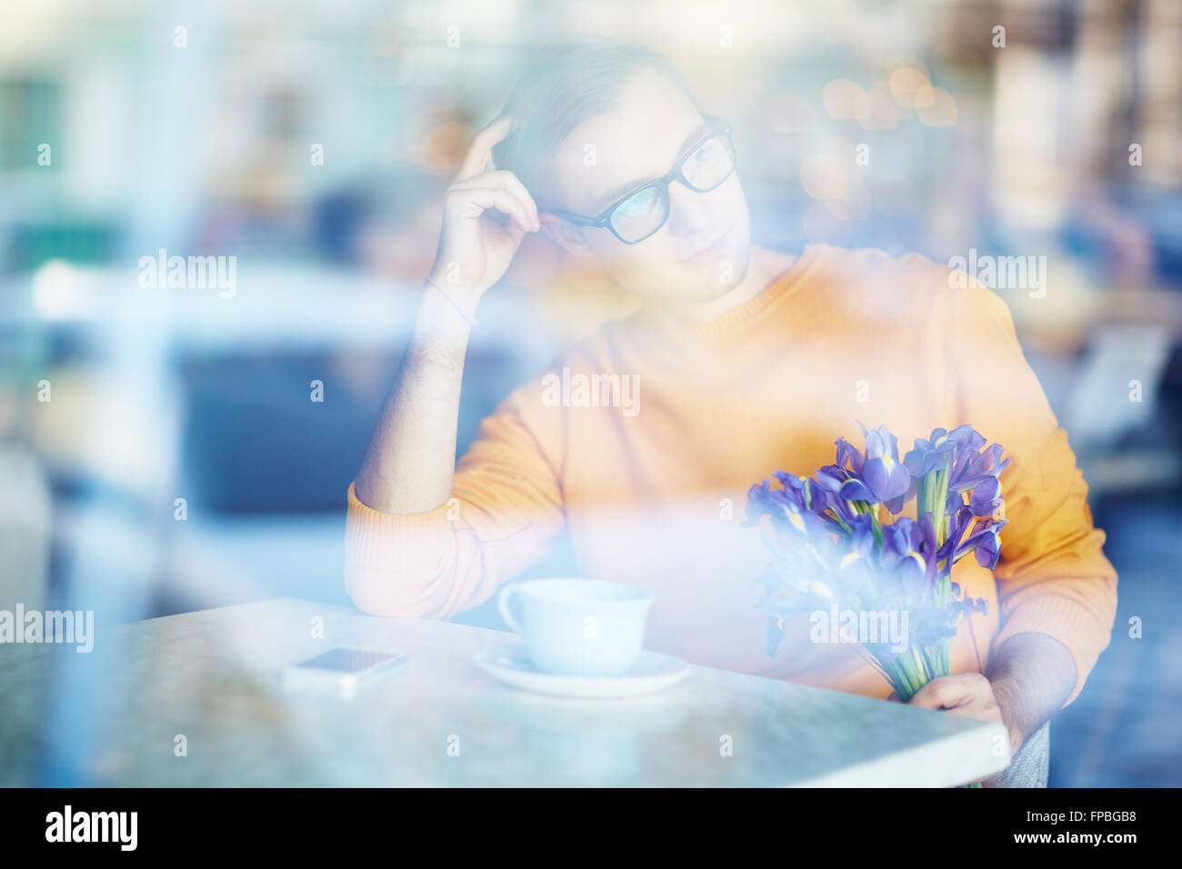 Young man with bouquet expecting his girlfriend at cafe - Stock Image
