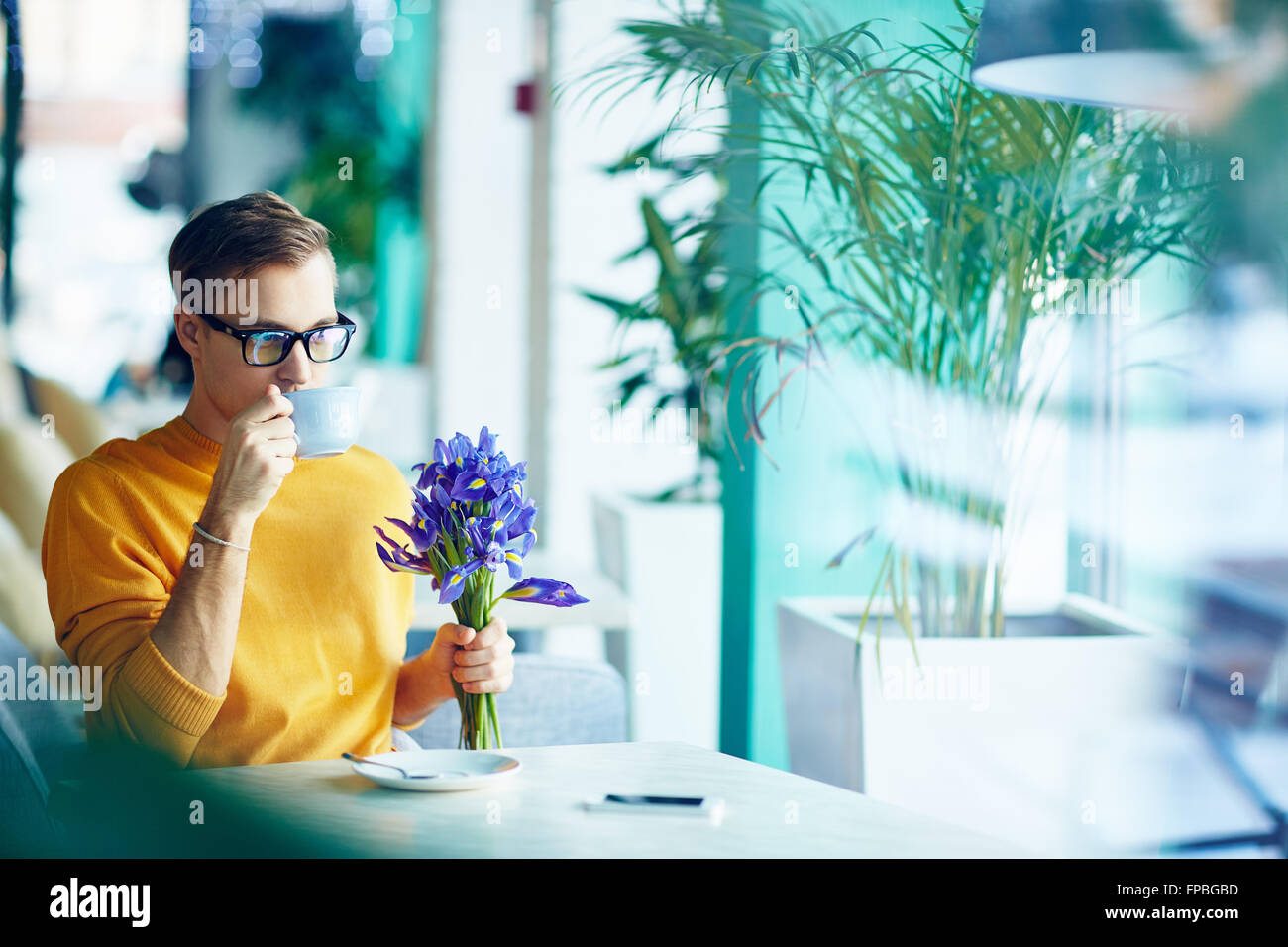 Young man with flowers drinking coffee at café - Stock Image