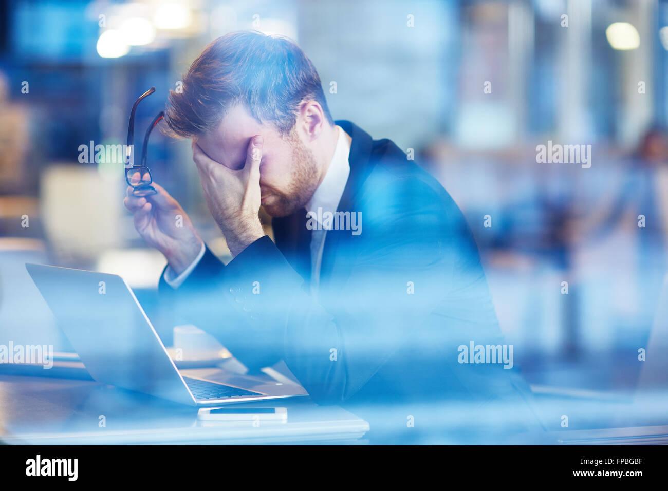 Depressed businessman sitting with laptop - Stock Image