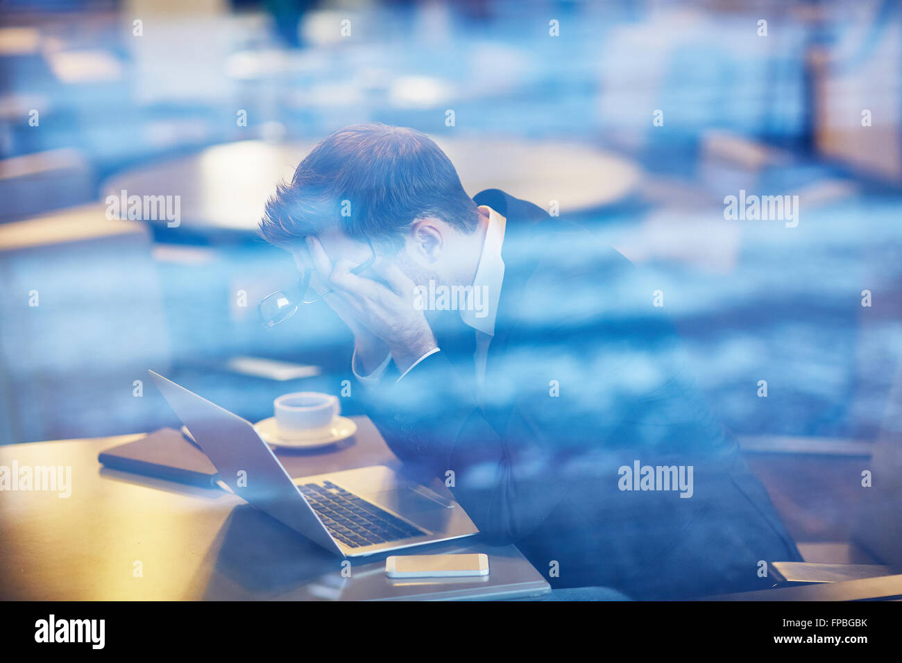 Stressed businessman sitting in front of laptop in cafe - Stock Image