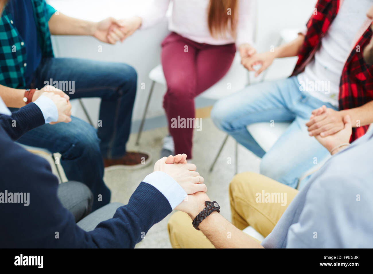 Group of people sitting in circle and supporting each other - Stock Image