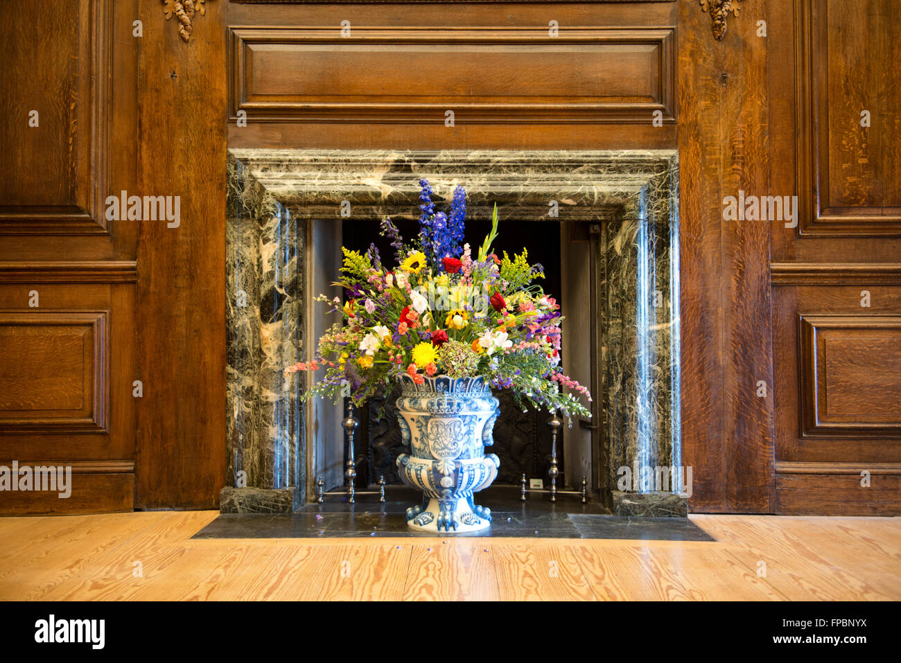 Flower arrangement of colorful summer blooms in a blue and white flower arrangement of colorful summer blooms in a blue and white pottery urn in a historical marble fireplace with wood paneling on the walls izmirmasajfo