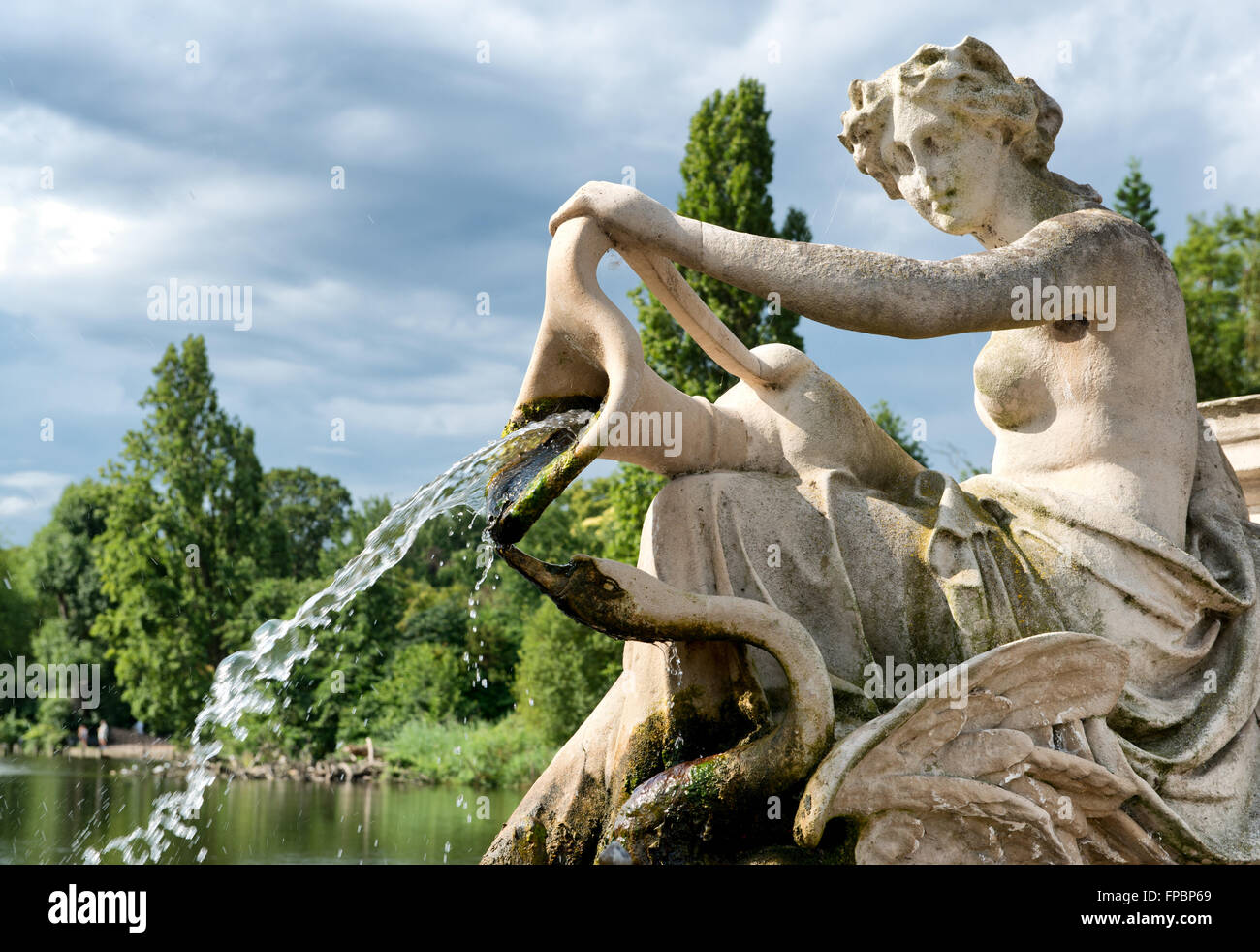 Detail of a classical stone fountain with a robed maiden holding an urn spilling a jet of cascading water into the - Stock Image