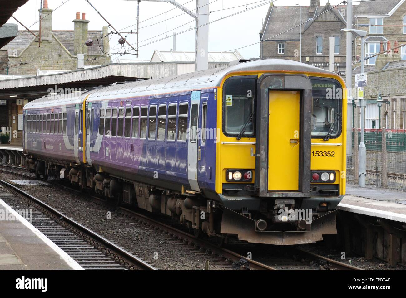 Two class 153 diesel unit in Northern livery on a passenger train leaving Carnforth railway station platform 1. - Stock Image