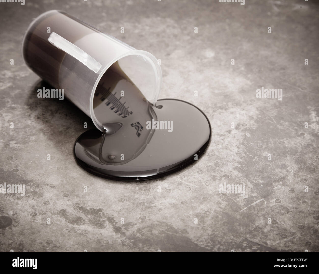 Crude oil spill on metal background - Stock Image