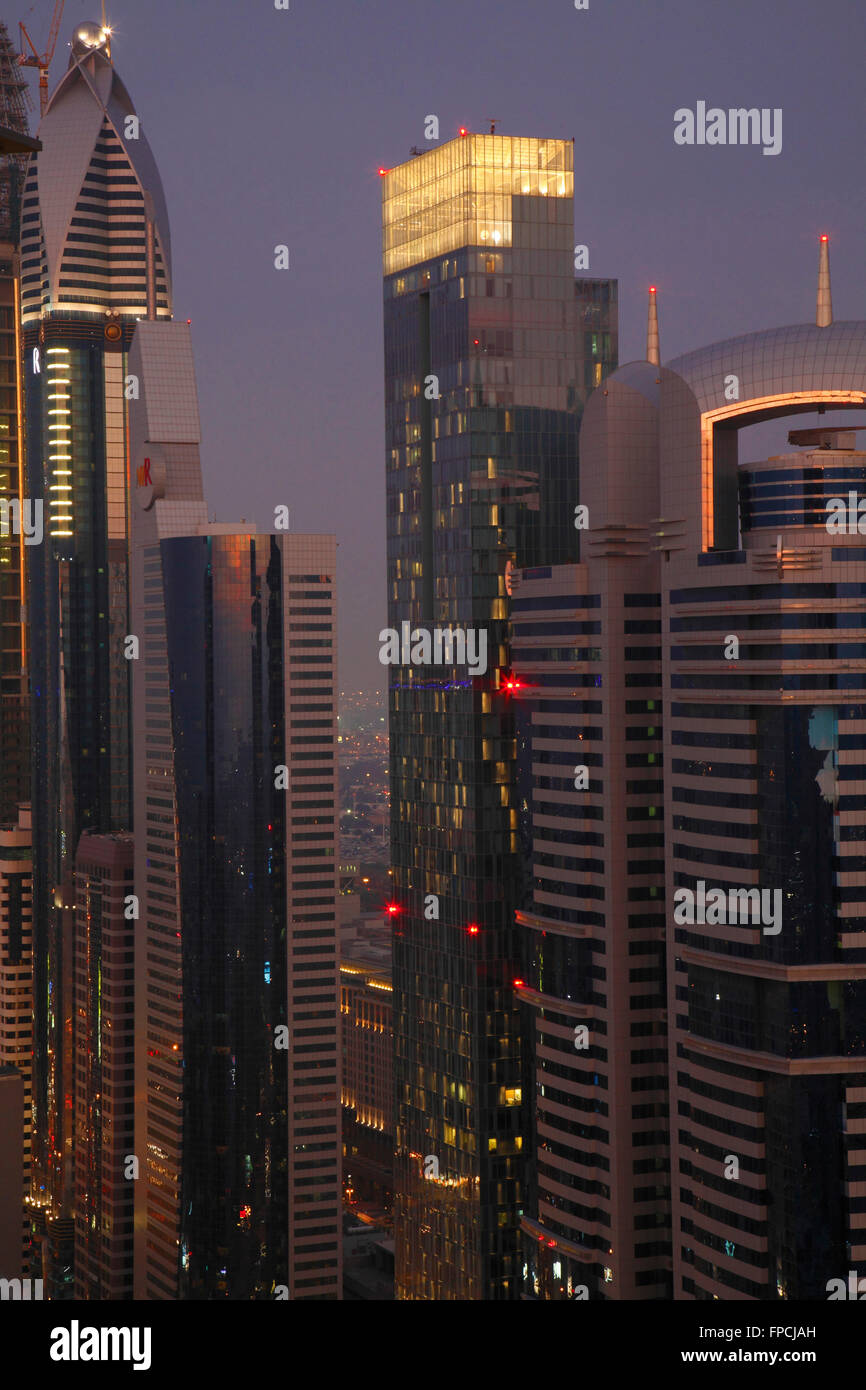An exterior view of towers in Dubai, at dusk. - Stock Image