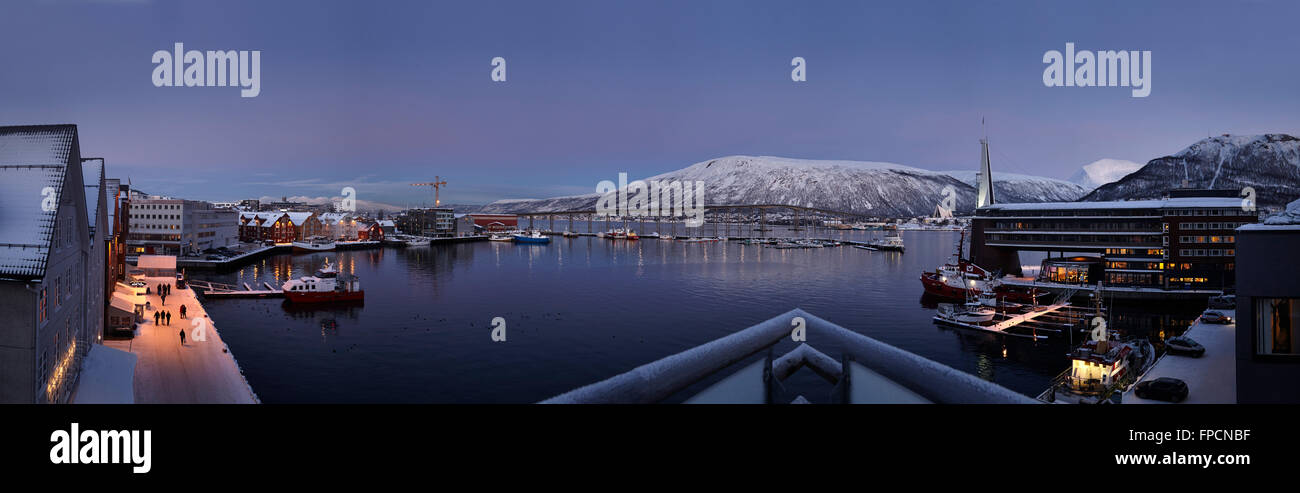 A view of the port, with buildings to the side and a snow capped mountains in the background. - Stock Image