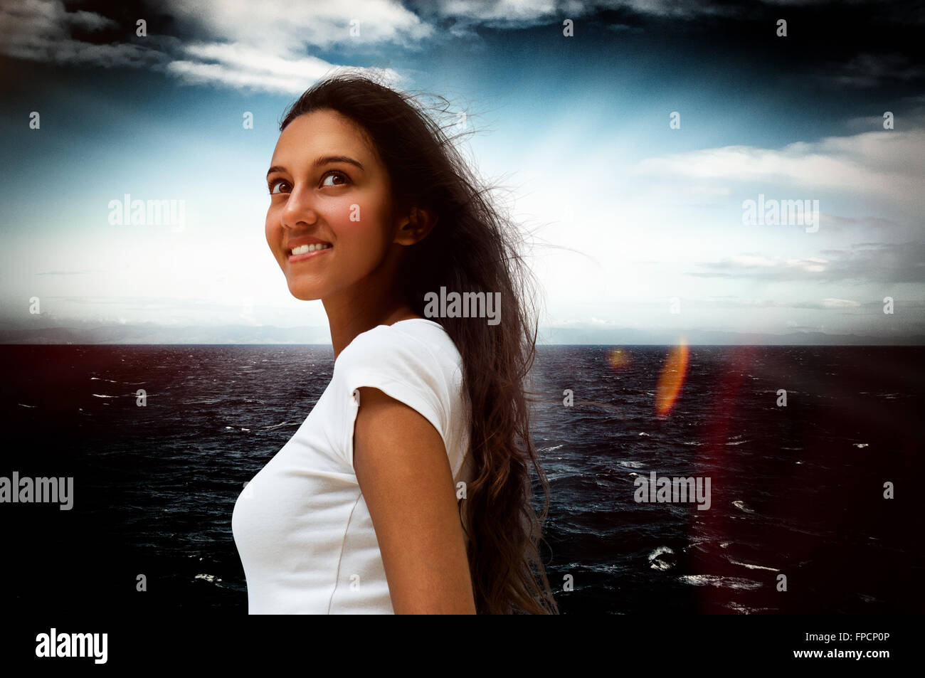 Smiling attractive young Indian woman standing looking up into the air with a dreamy expression against a dark dramatic Stock Photo
