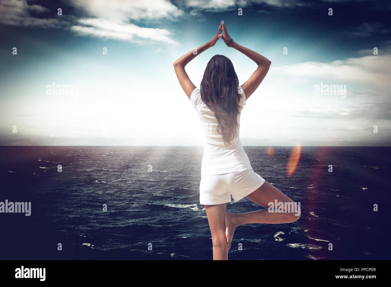 Dramatic mystical image with flare effect and vignette of a young woman practising yoga at the sea standing in a - Stock Image