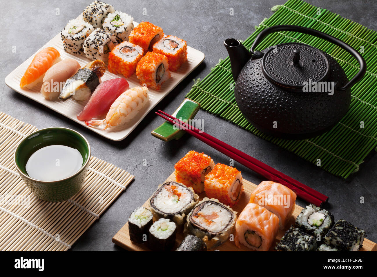 Set of sushi and maki roll and green tea on stone table - Stock Image