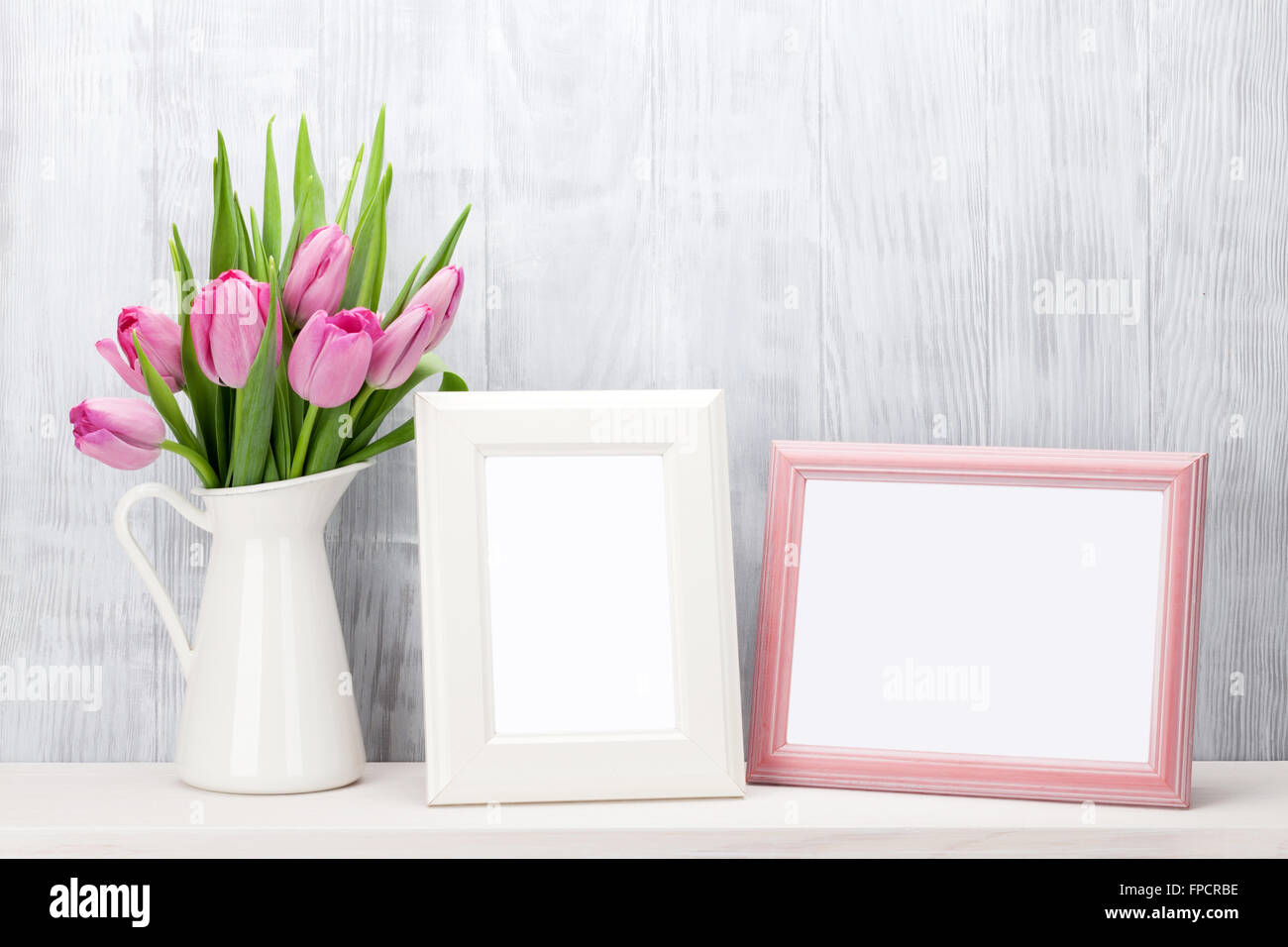 Fresh pink tulip flowers bouquet and blank photo frames with copy fresh pink tulip flowers bouquet and blank photo frames with copy space on shelf in front of wooden wall izmirmasajfo