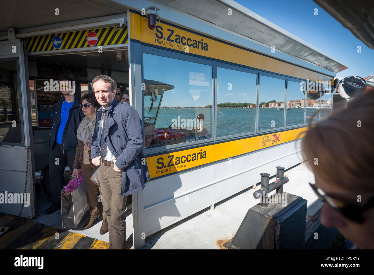 Male and female passengers waiting for people leaving the ferry boat onto the platform at S.Zaccaria in Canal Grande - Stock Image