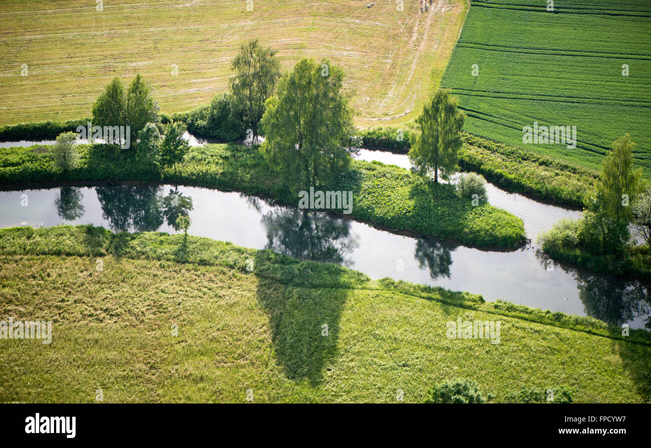 Aerial view from above of a scenic landscape with a river dividing around an island with trees in rural farmland - Stock Image