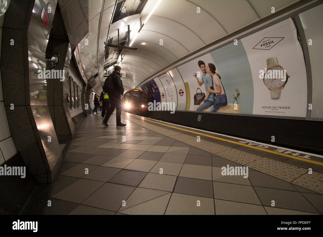 Advertising on London Underground with tube network train, Central Line,  with Fossil watch advert on poster - Stock Image