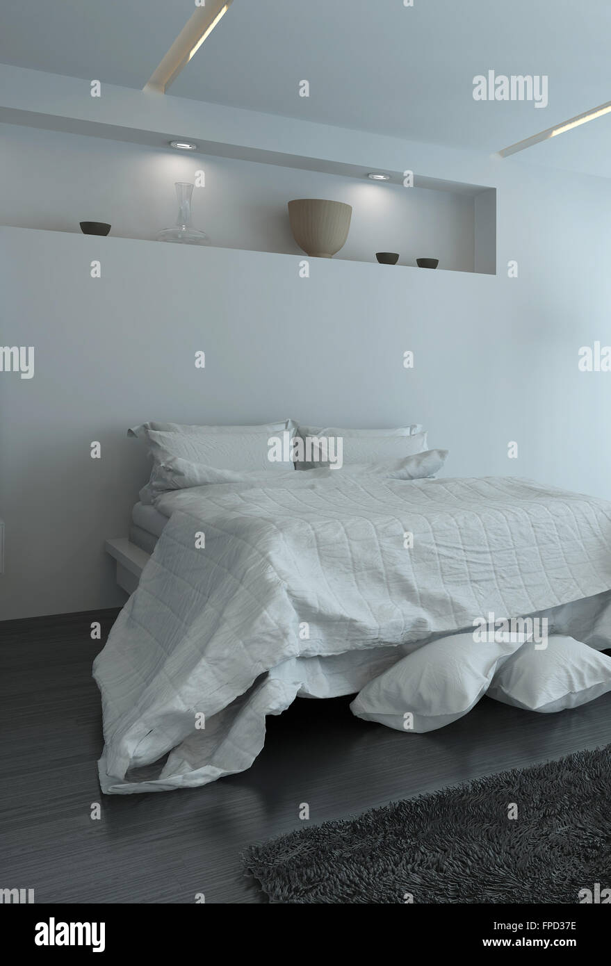 Double bed with large duvet and extra pillows on the floor in a modern white bedroom interior illuminated by recessed Stock Photo