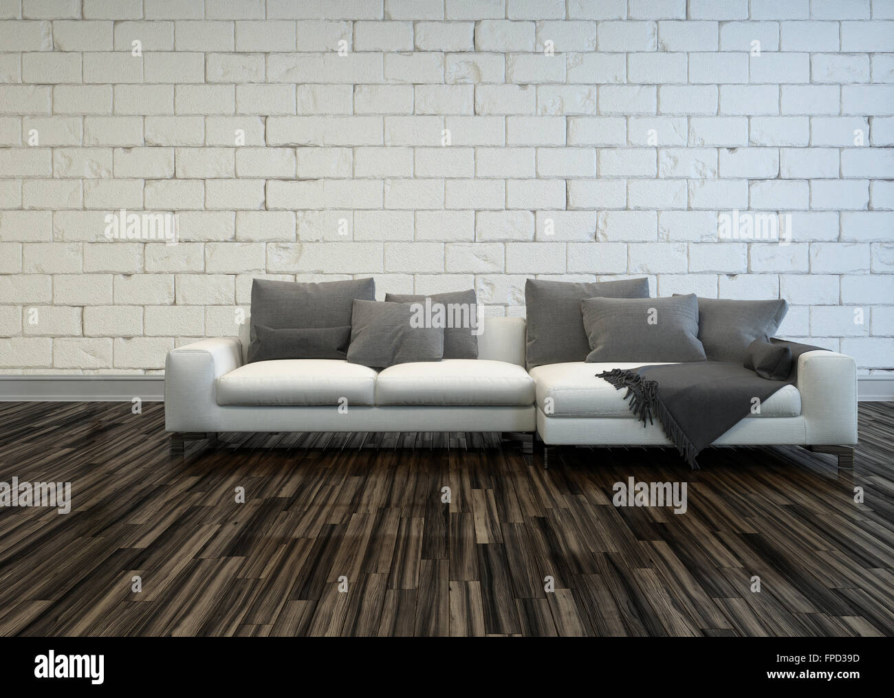 Rustic living room interior with a large white sofa with grey cushions on a bare wooden parquet floor against a Stock Photo