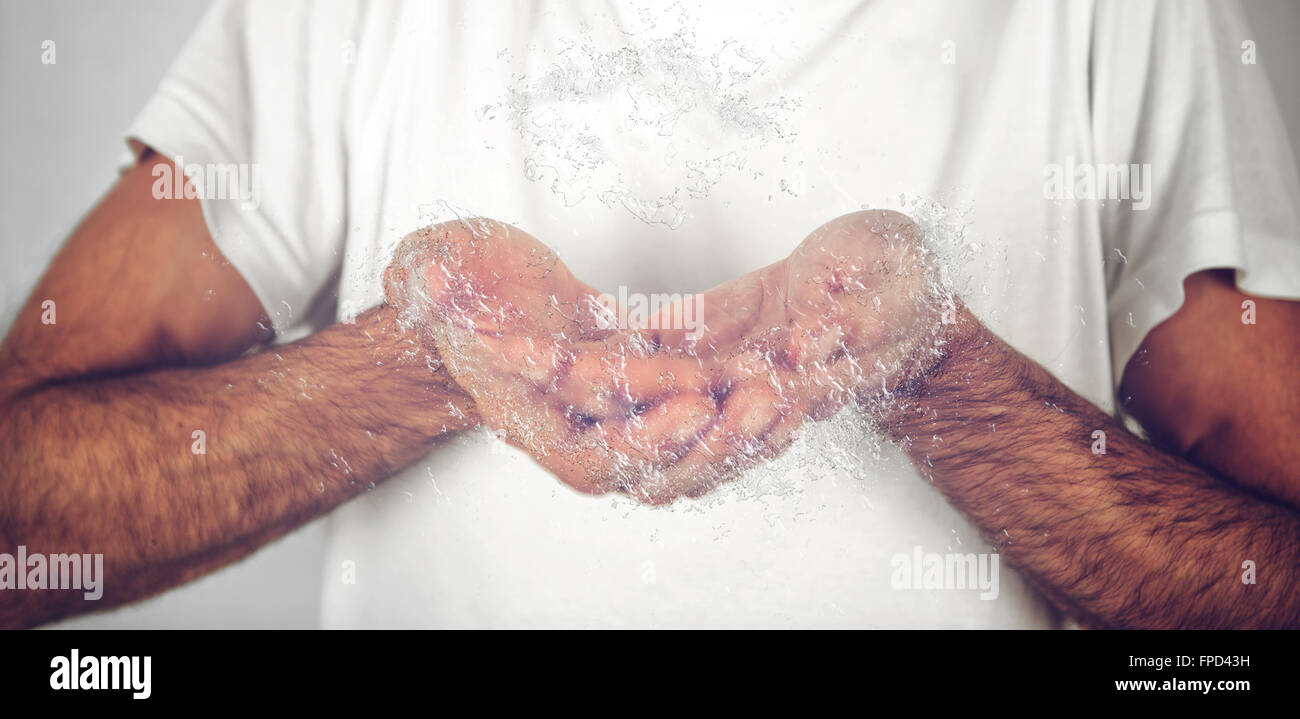 Close up Hairy man in White Shirt Catching Water Using his Bare Hands. - Stock Image