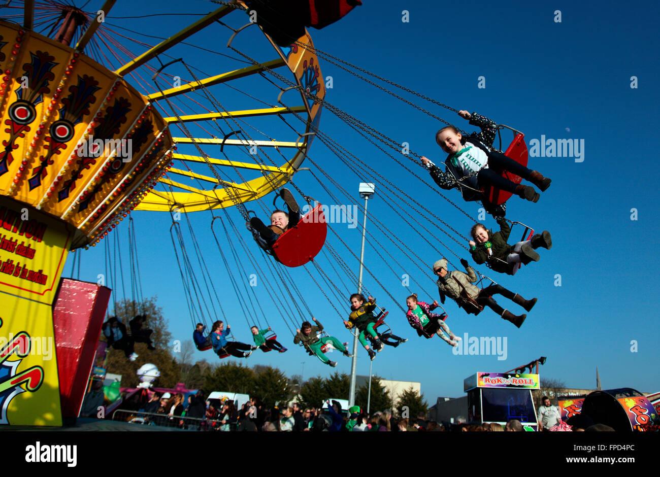 Children enjoy the swings at Carrickmacross funfair on St Patricks Day - Stock Image