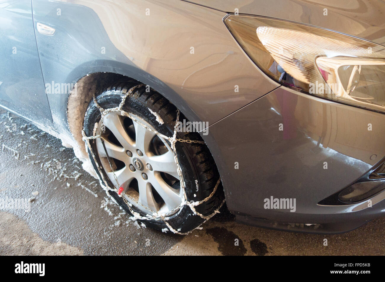 Snow chains on a car tyre in winter, Switzerland Europe - Stock Image