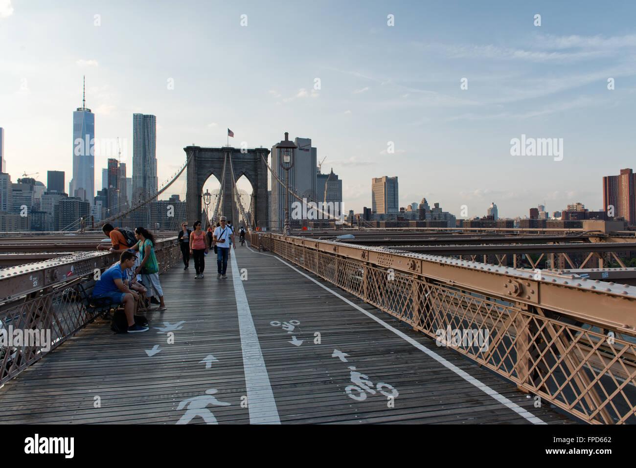 People Walking Across Brooklyn Bridge In The Pedestrian Lane In